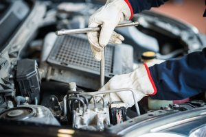 Detail of a mechanic at work on car engine
